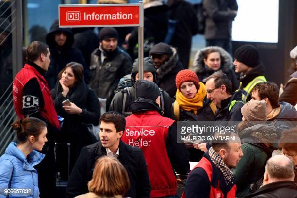 Travellers wait for information at Berlin's main station on January 18 as Germany's rail operator Deutsche Bahn said it was suspending all...