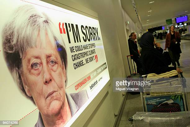 Travellers wait for their baggage next to an advertising sign showing a picture of grown old German Chancellor Angela Merkel and reading 'I'm sorry...