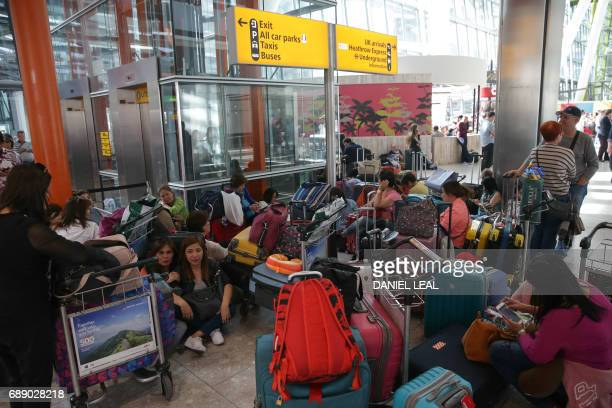 Travellers wait stranded at Heathrow Airport Terminal 5 after British Airways flights where cancelled at Heathrow Airport in west London on May 27...