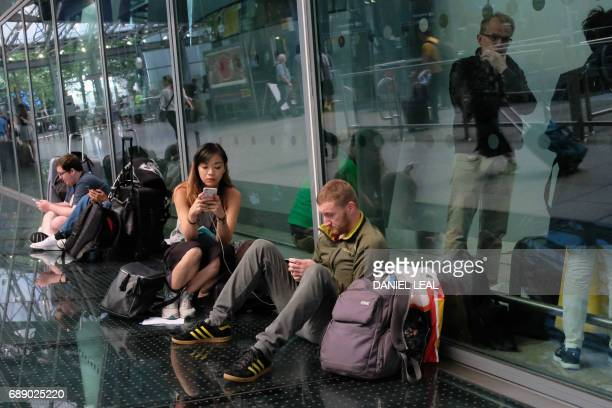 Travellers wait stranded outside Heathrow Airport Terminal 5 after British Airways flights where cancelled at Heathrow Airport in west London on May...