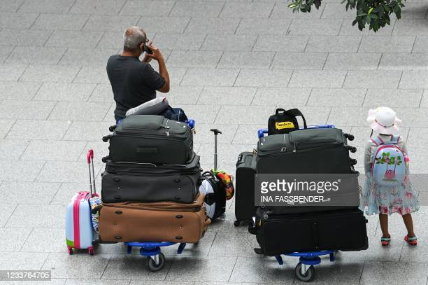 Travellers wait with their suitcases before checking in on July 2, 2021 at the airport of Duesseldorf as summer holidays begin in this western German...