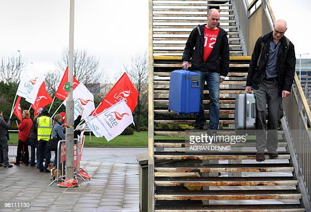 Travellers walk down a flight of stairs from an overpass close to an official picket line at London Heathrow Airport during the third day of a...