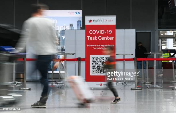 Travellers walk past a coronavirus COVID-19 rapid test center on July 2, 2021 at the airport of Duesseldorf as summer holidays begin in this western...