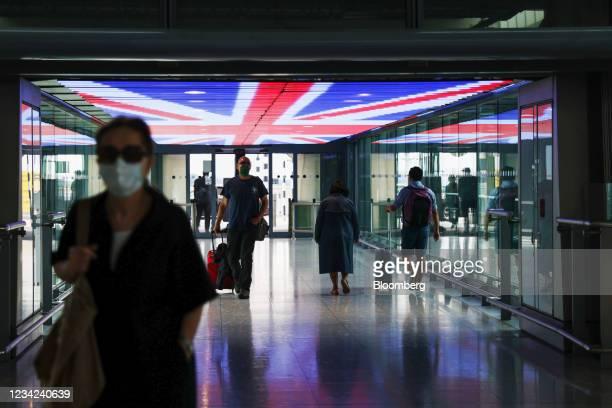 Travellers walk underneath a British Union Flag at Terminal 5, London Heathrow Airport Ltd. In London, U.K., on Tuesday, July 27, 2021. International...