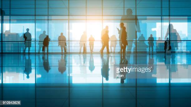 travellers walking in modern airport hallway - public building stock pictures, royalty-free photos & images