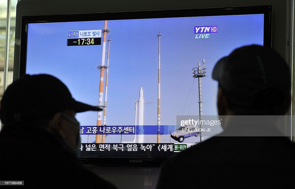 Travellers watch a TV screen broadcasting live footage on South Korea's third attempt of a rocket launch, at a railway station in Seoul on November 29, 2012
