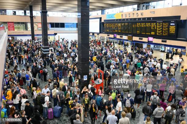Travellers watch the announcement boards in Euston rail station during the busy morning rush hour on August 09 2019 in London England The train...