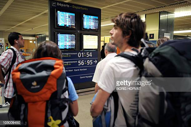 Travellers watche departure screens on July 21, 2010 at the Orly airport, outside Paris as a strike by air traffic controllers disrupted travel...