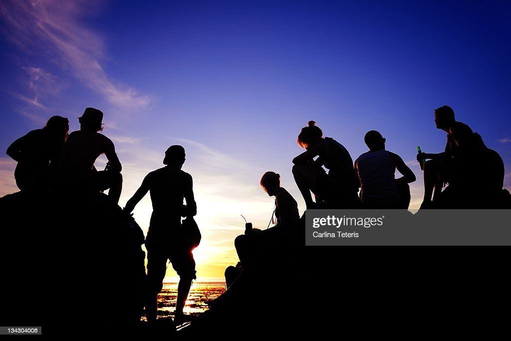 Travellers watching sunset : Stock Photo