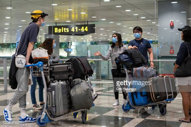 Travellers wearing face masks gather after they exit from the arrival hall of Changi Airport on March 23, 2020 in Singapore. Singapore is imposing a...