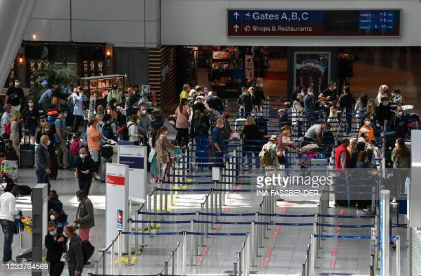 Travellers wearing face masks queue at the check-in counters on July 2, 2021 at the airport of Duesseldorf as summer holidays begin in this western...