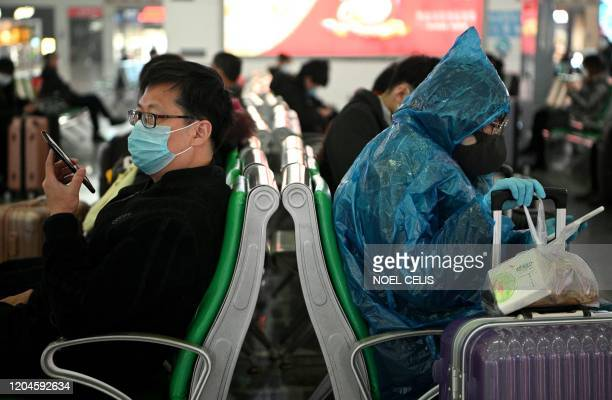 Travellers wearing face masks sit on benches at Changsha railway station in Changsha, Hunan province, bordering Hubei province, on March 2, 2020. -...