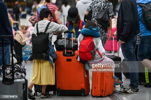 Travellers wearing face masks sit on their suitcases at the check-in counters on July 2, 2021 at the airport of Duesseldorf as summer holidays begin...