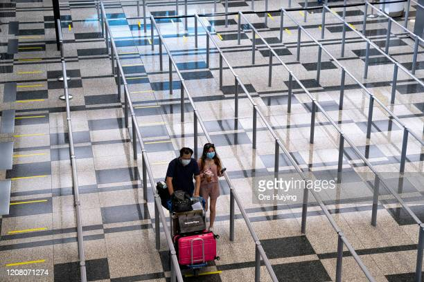 Travellers wearing face masks walk towards the taxi stand at the arrival hall of Changi Airport on March 23 2020 in Singapore Singapore is imposing a...