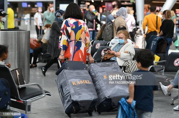 Travellers wearing face masks walk with their suitcases on July 2, 2021 at the airport of Duesseldorf as summer holidays begin in this western German...