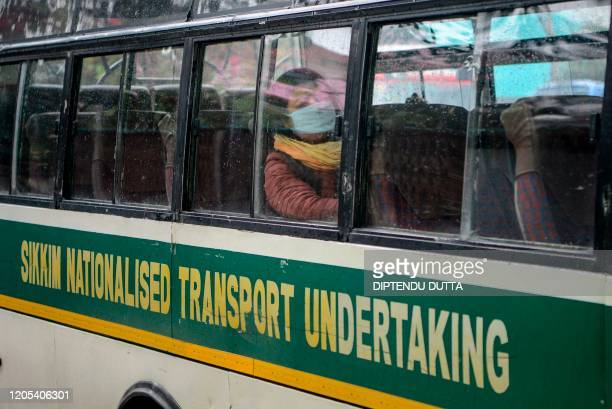 Travellers wearing facemasks sit in a bus at the Sikkim Nationalised Transport parking following a ban put by the Sikkim government on all foreign...