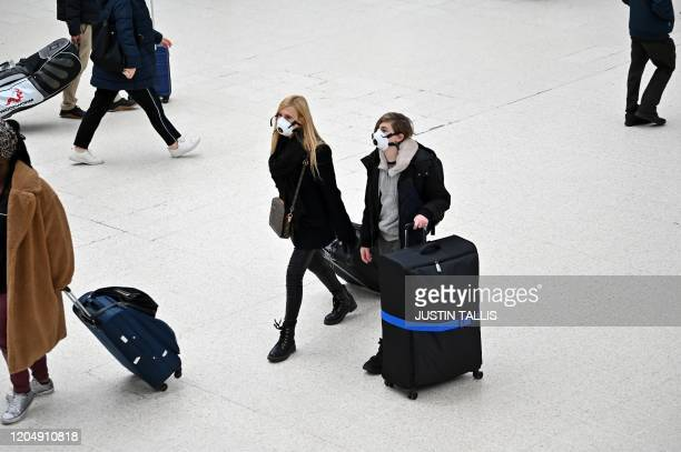 Travellers wearing protective face masks pull their suitcases while walking across the concourse at London Victoria train station in central London...