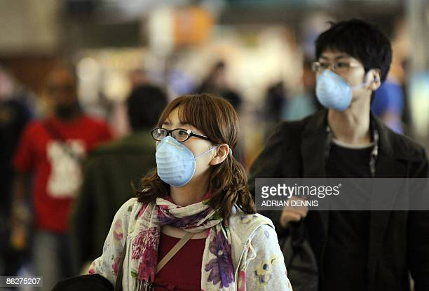 Travellers wearing protective masks wait for their flights at Barcelona International Airport on April 29 2009 Spain reported on April 28 2009 a...