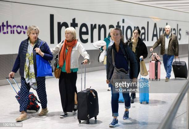 Travellers who had been aboard the covid19 stricken Braemar cruise ship operated by Fred Olsen Cruise Lines react as they arrive at Heathrow Airport...