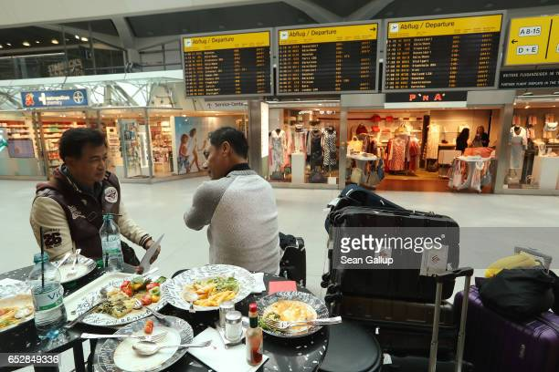 Travellers whose flight to Bangkok was cancelled sit near the arrivals and departures board during a strike by ground personnel at Tegel Airport on...