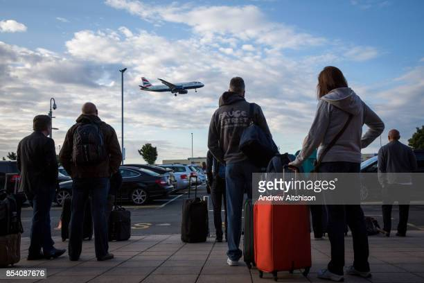 Travellers with their suitcases wait outside the Heathrow Premier Inn for the terminal shuttle bus to take them to their required terminal at...