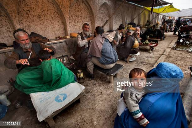 Travelling barbers set up shop around the Pole Kheshti Mosque the city's principle place of workship May 7 2009 in Kabul's Central Market Afghanistan...