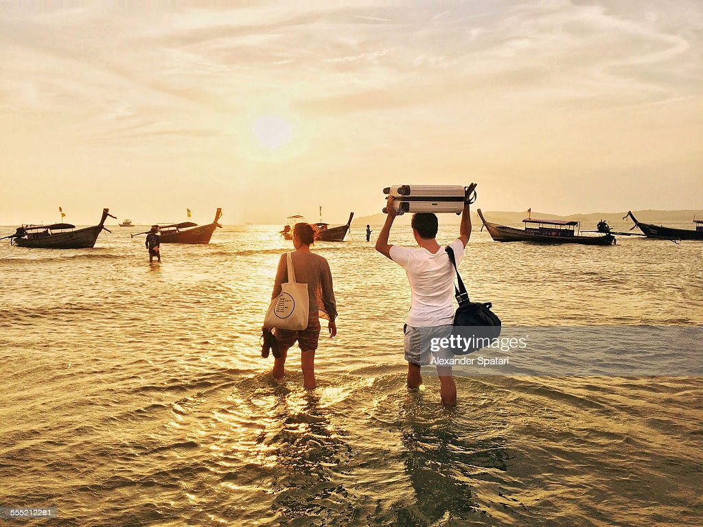 Travelling couple in Thailand walking in the ocean to the longtail boat with their luggage bags above the head : Foto stock