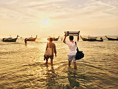 Travelling couple in Thailand walking in the ocean to the longtail boat with their luggage bags above the head