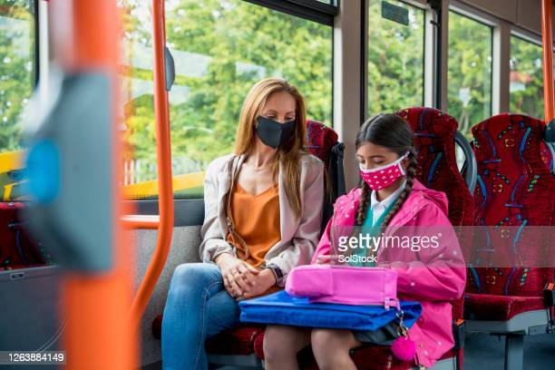 travelling home from school during covid 19 - bus stock pictures, royalty-free photos & images