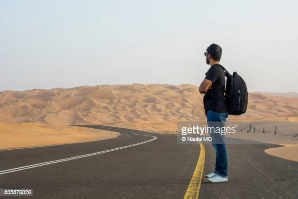 travelling man waiting on liwa desert road, abu dhabi, united arab emirates - stranded stock photos and pictures