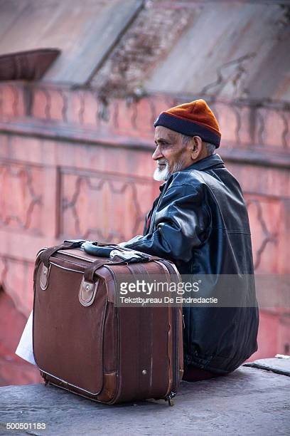 CONTENT] Travelling old muslim man wearing a leather jacket with a big suitcase sitting and waiting outside the Jama Masjid the largest mosque in...