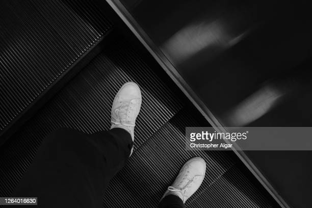 travelling on an escalator - silver shoe stock pictures, royalty-free photos & images