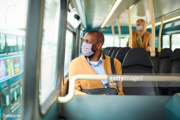 travelling to work with a facemask - public transport stock pictures, royalty-free photos & images