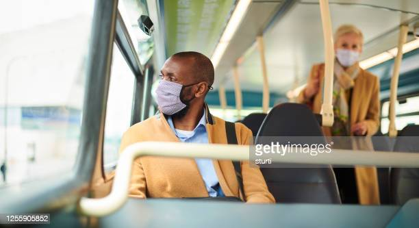travelling to work with a facemask - bus stock pictures, royalty-free photos & images