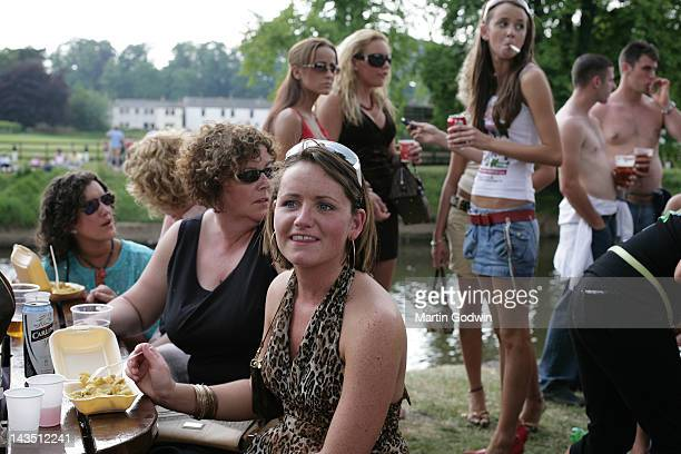 Travelling women eating chips and drinking beer and coke by the river at the Appleby Horse Fair Appleby Cumbria 9th June 2007