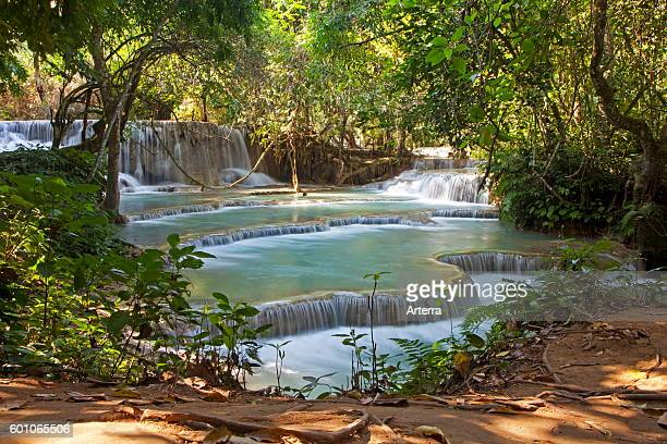 Travertine cascades and turquoise blue pools of the Kuang Si Falls / Kuang Xi / Tat Kuang Si Waterfalls near Luang Prabang Louangphrabang Province...