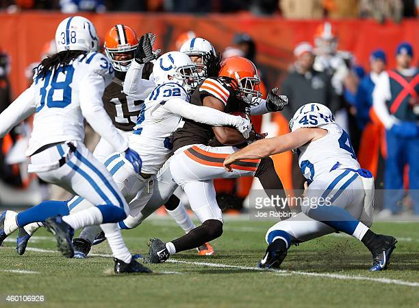 Travis Benjamin of the Cleveland Browns gets wrapped up by Colt Anderson and Matt Overton of the Indianapolis Colts during the second quarter at...