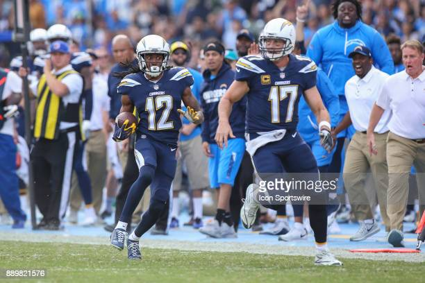 Travis Benjamin of the Los Angeles Chargers runs the ball as Philip Rivers of the Los Angeles Chargers lead blocks for him during a NFL game between...