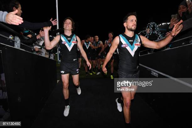 Travis Boak captain of Port Adelaide and Jared Polec of Port Adelaide head down the race during the round 13 AFL match between Port Adelaide Power...