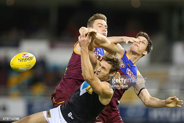 Travis Boak of the Power and Harris Andrews and Justin Clarke of the Lions compete for the ball during the round seven AFL match between the Brisbane...