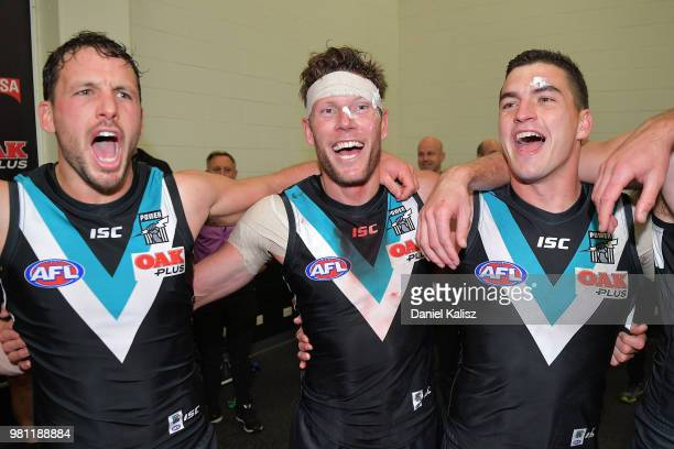 Travis Boak of the Power Brad Ebert of the Power and Tom Rockliff of the Power sing the club song after defeating the Melbourne Deamons during the...