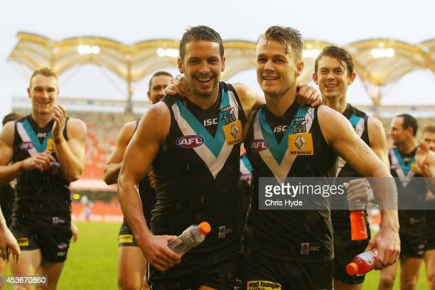 Travis Boak of the Power celebrates winning and playing his 150th game with team mate Robbie Gray during the round 21 AFL match between the Gold...