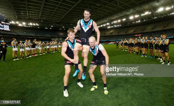Travis Boak of the Power is chaired from the field after his 300th match by teammate Ollie Wines and Sam Powell-Pepper during the 2021 AFL Round 19...