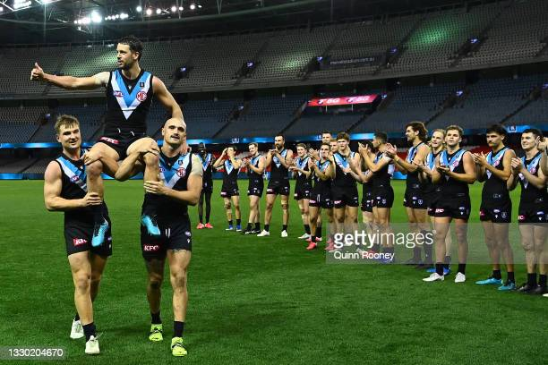Travis Boak of the Power is chaired off by Ollie Wines and Sam Powell-Pepper of the Power in his 300th game during the round 19 AFL match between...