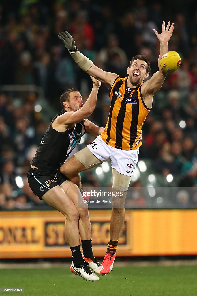 Travis Boak of the Power is injured in a contest with Luke Hodge of the Hawks during the round 16 AFL match between the Port Adelaide Power and the Hawthorn Hawks at Adelaide Oval on July 7, 2016 in Adelaide, Australia.