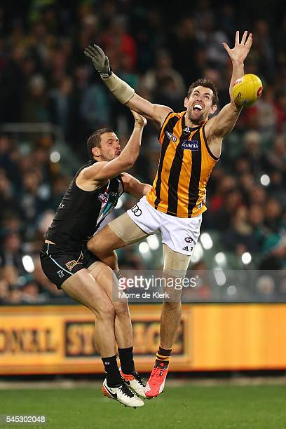 Travis Boak of the Power is injured in a contest with Luke Hodge of the Hawks during the round 16 AFL match between the Port Adelaide Power and the...