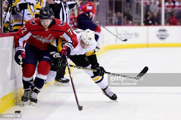 Travis Boyd of the Washington Capitals and Garrett Wilson of the Pittsburgh Penguins battle for the puck in the first period at Capital One Arena on...
