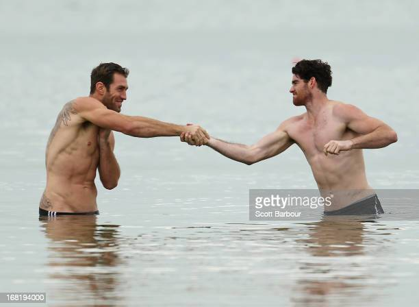 Travis Cloke and Tyson Goldsack of the Magpies shake hands as they wade in the water during a Collingwood Magpies AFL recovery session at St Kilda...