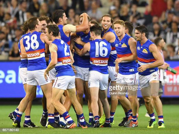 Travis Cloke of the Bulldogs is congratulated by team mates after kicking a goal during the round one AFL match between the Collingwood Magpies and...