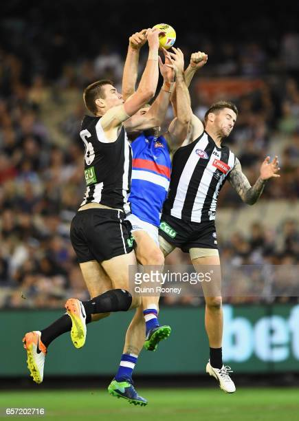 Travis Cloke of the Bulldogs marks in between Mason Cox and Jeremy Howe of the Magpies during the round one AFL match between the Collingwood Magpies...